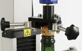 Gripping the cork securely for extraction force and torque measurement is essential